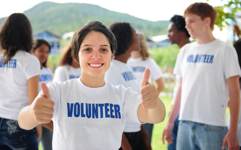 Happy volunteer girl in a group outdoors during daytime