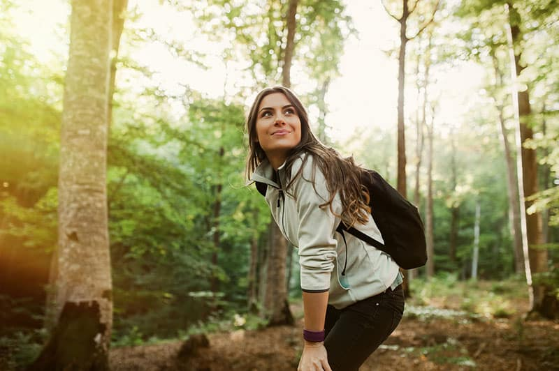 happy woman hiking in woods