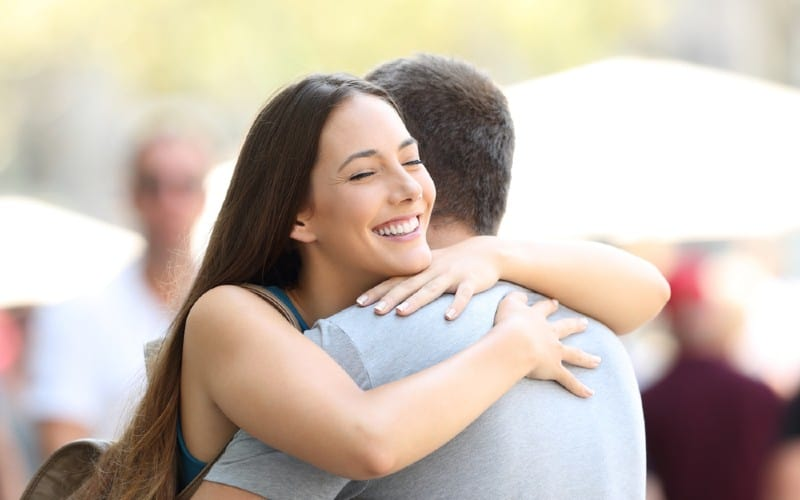 Happy woman hugging man outdoors duting daytime