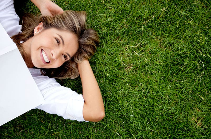 happy woman laying on the grass