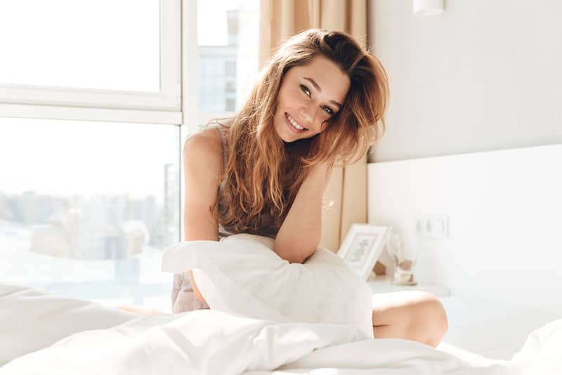 happy woman sitting on the bed