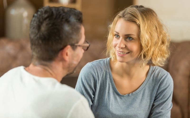 Happy blonde woman talking to a man while sitting in front of him