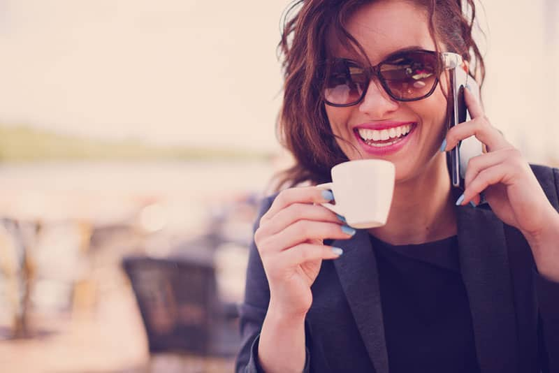 happy woman wearing sunglasses and cup of coffee