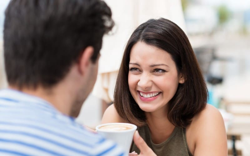 Happy woman sitting in front of a man with coffe cup during daytime