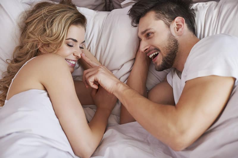 happy young couple tickeling in bed