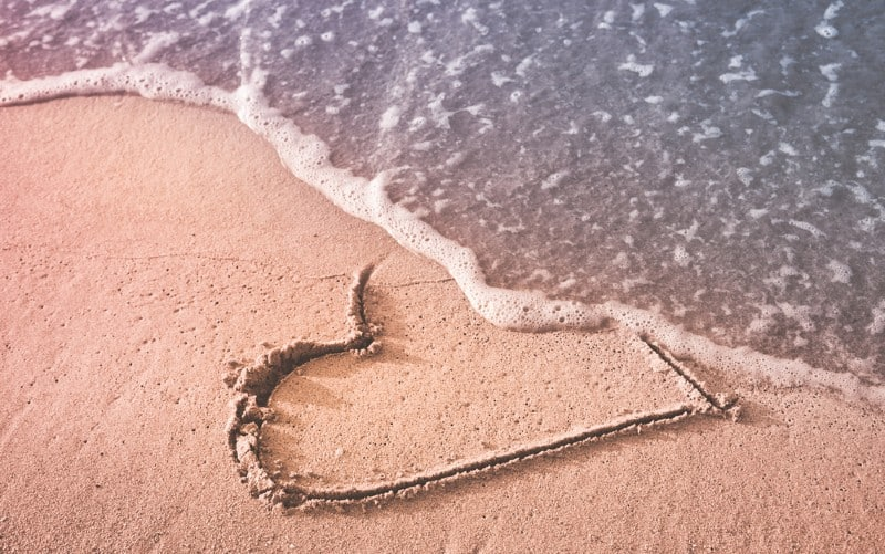 Heart drawn on the beach sand being washed away by a wave