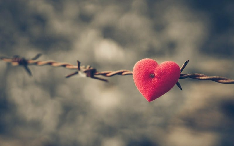 Red heart on a barbed wire and cloudy sky background