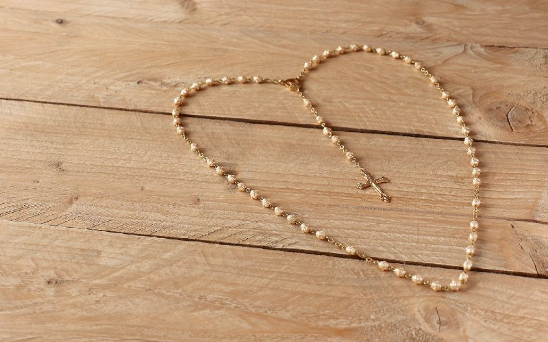 Heart shaped prayer rosary on wooden background
