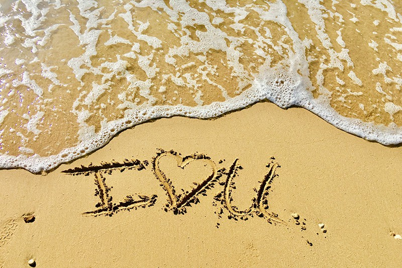 i love you text on the sand near the water