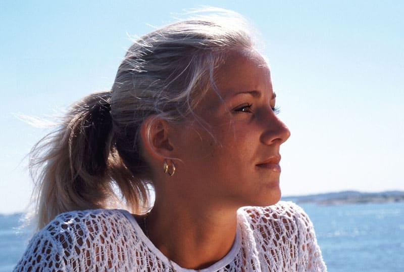 introspecting blonde woman's face in focus near the body of water