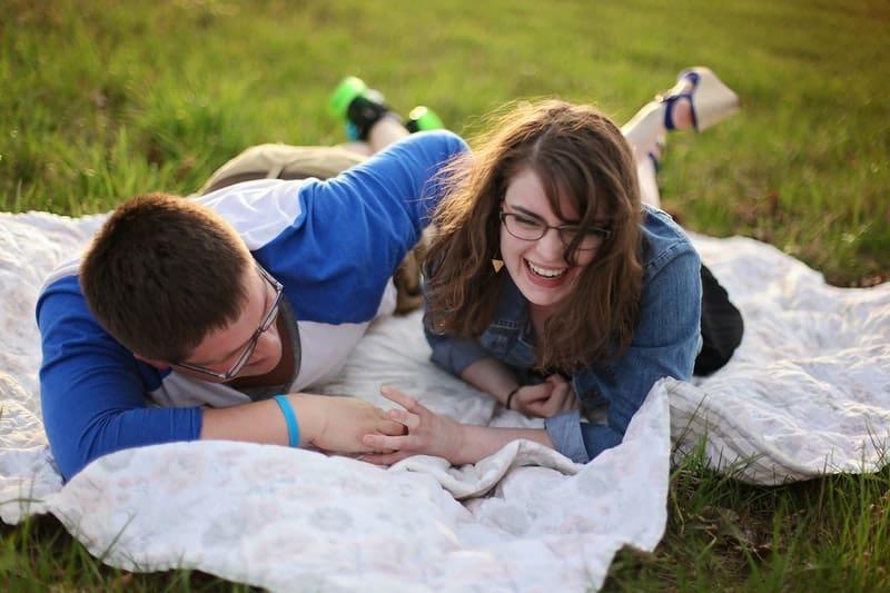 laughing couple on picnic mat wearing denim tops
