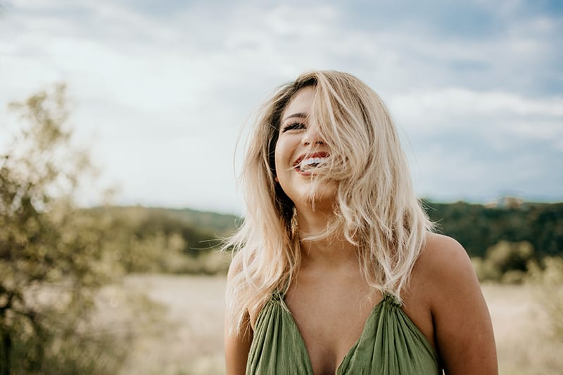 laughing woman with hair covering half of her face