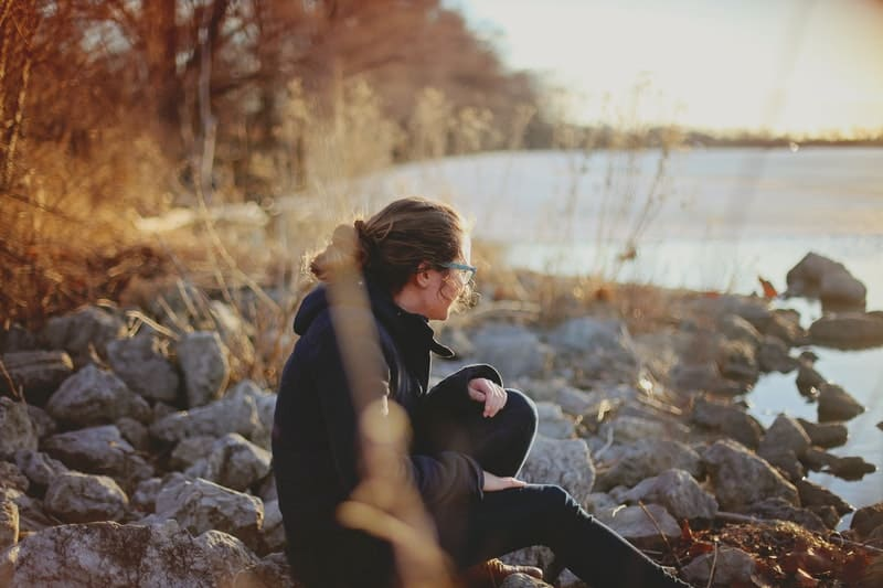 lonely woman in autumn sitting near the lake