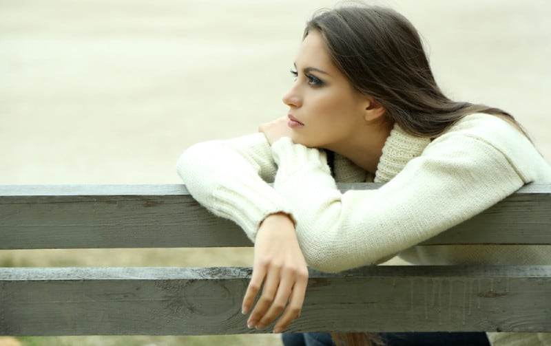Lonely young woman sitting on a bench