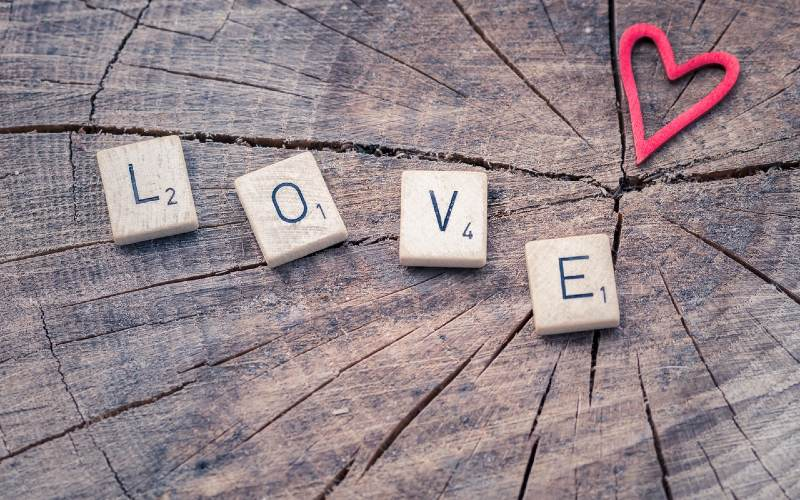 The word Love written with scrabble piecesand a red heart on a wooden background