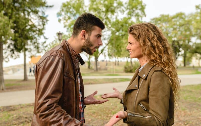 Man and woman wearing brown jackets arguing outdoors during daytime