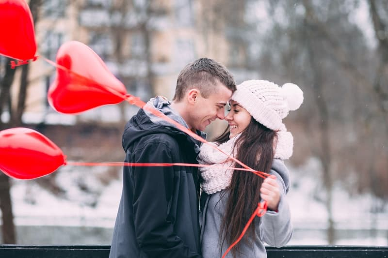 man and woman bringing 3 red heartshaped balloons