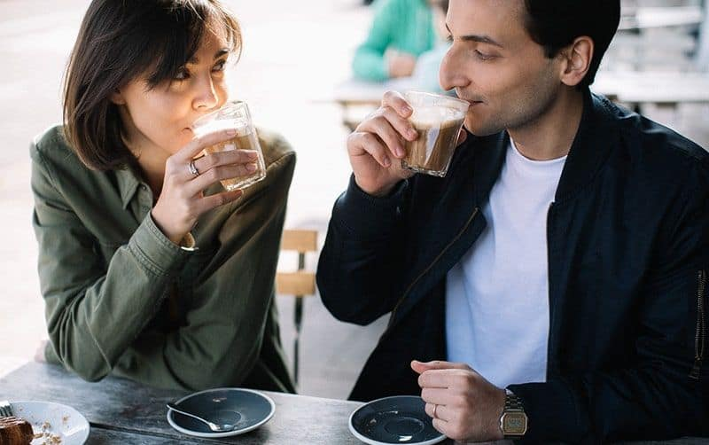 Man and woman drinking coffee from plastic cups