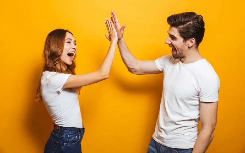 Happy man and woman giving high five stanging against orange wall