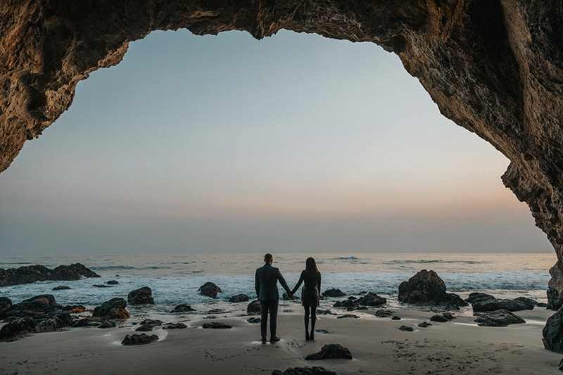 man and woman hold hands at beach with rocks