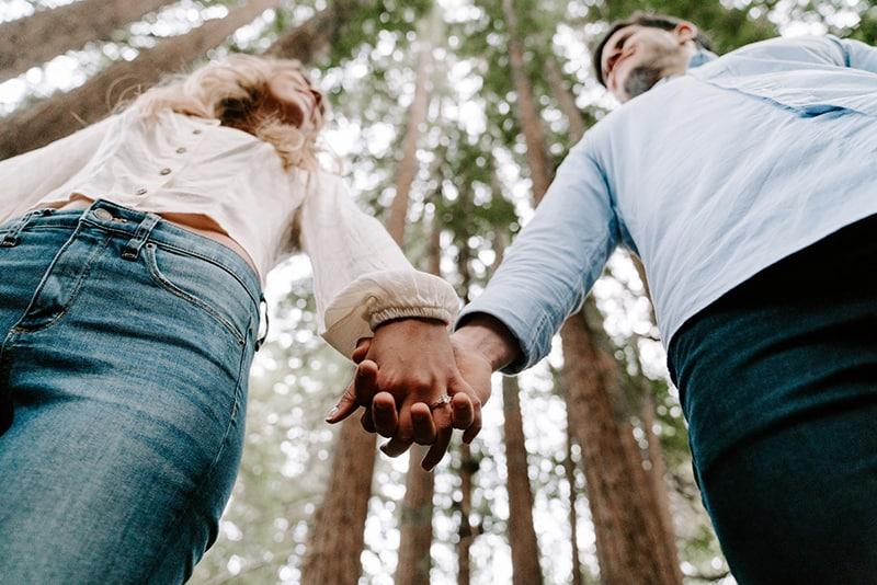 man and woman holding each others hands while standing beside the trees