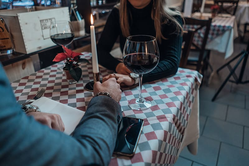 man and woman holding across the table with glasses of wine on it