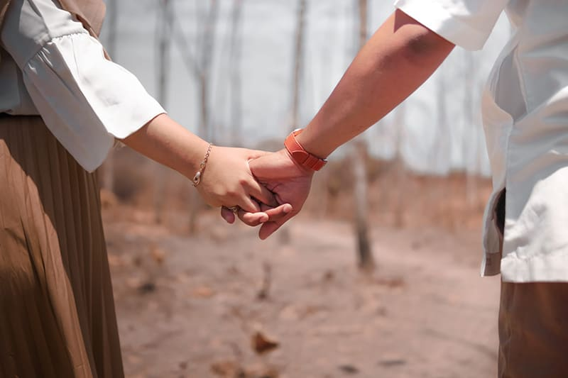 man and woman holding hands in the wood during daytime