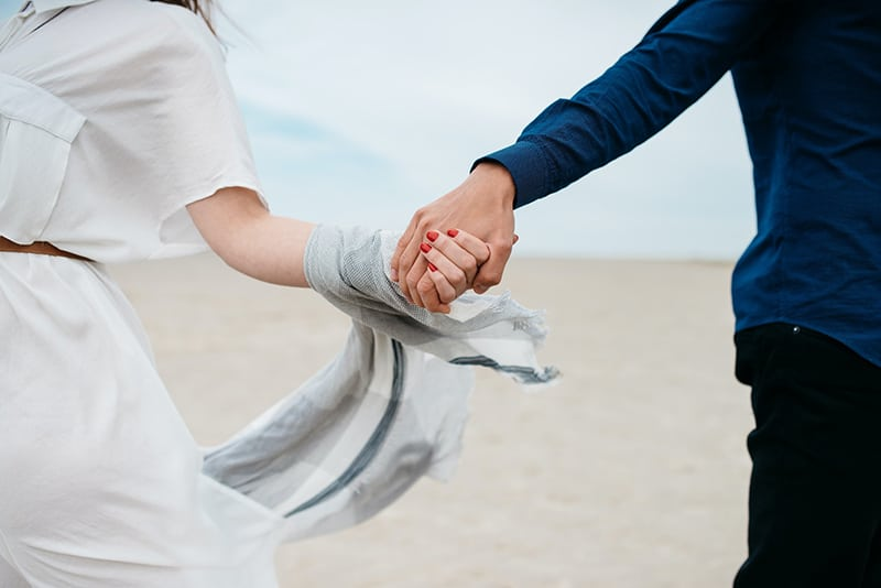 man and woman holding hands together during daytime