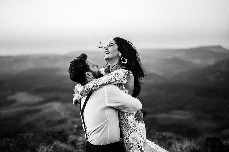 man and woman hugging near hill