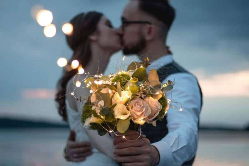 man and woman kissing holding white flowers