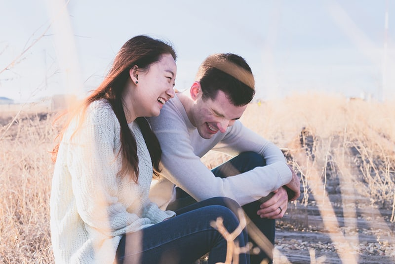 man and woman laughing while sitting in the nature