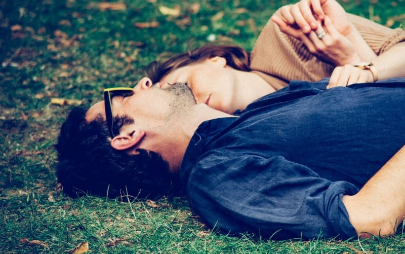 Man and woman lying on grass during daytime
