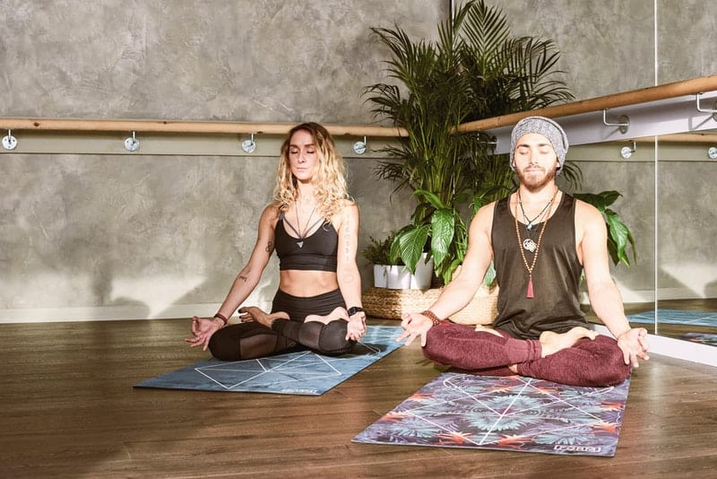 man and woman meditating on a mat and a plant nearby