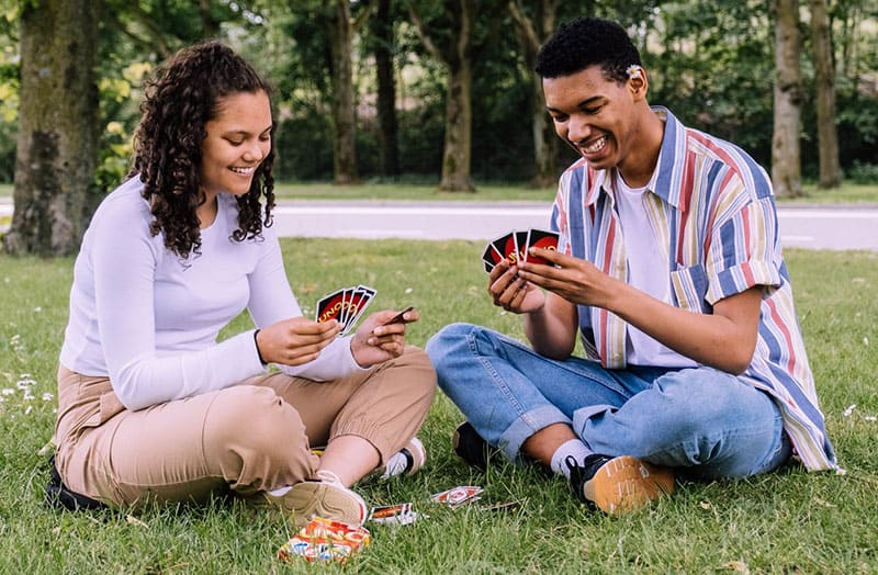 man and woman playing cards sitting in the green grass