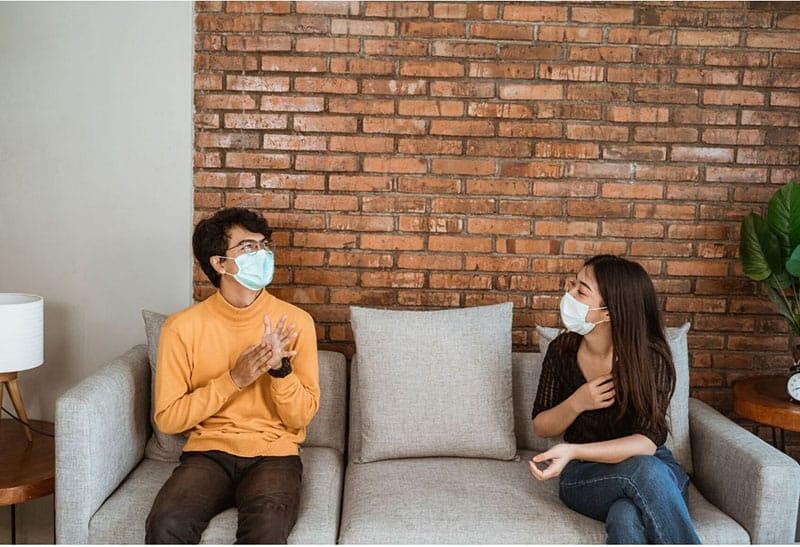 man and woman seated apart in a sofa near brick walls