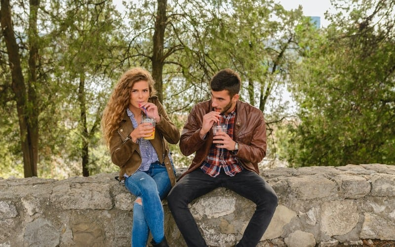 Man and woman sitting and drinking juice in nature during daytime