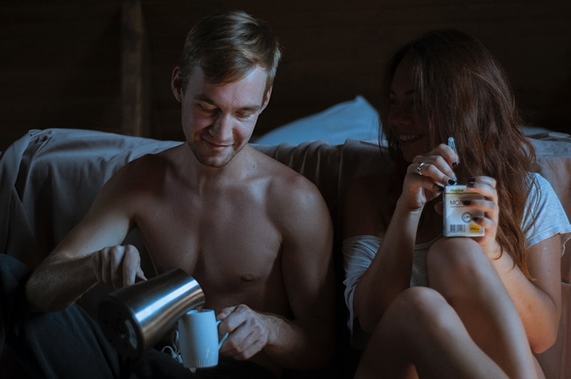 man and woman sitting beside bed while man pouring coffee
