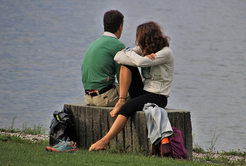 man and woman sitting beside the body of water during daytime