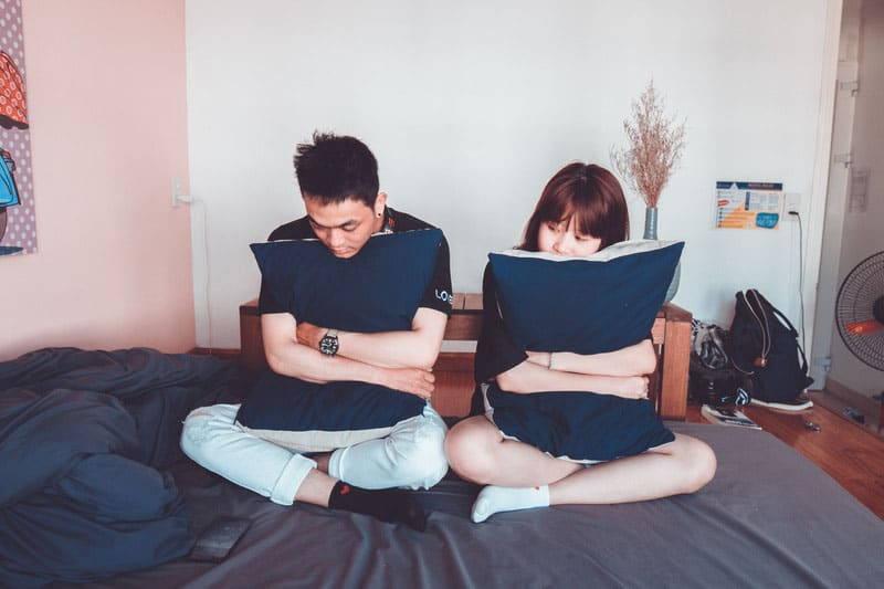 man and woman sitting on bed both embracing blue pillows