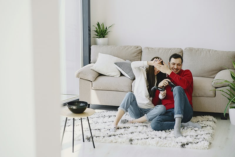 man and woman sitting on carpet while laughing