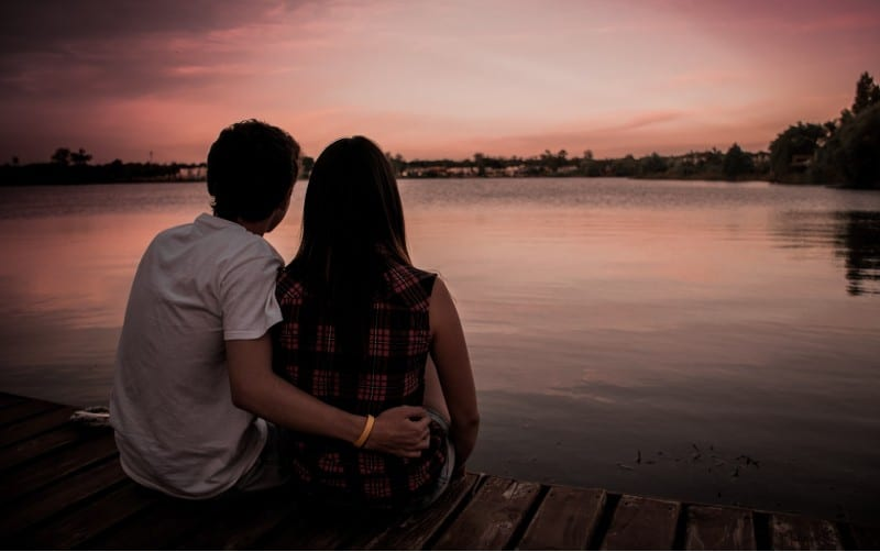 man and woman sitting on dock in the evening