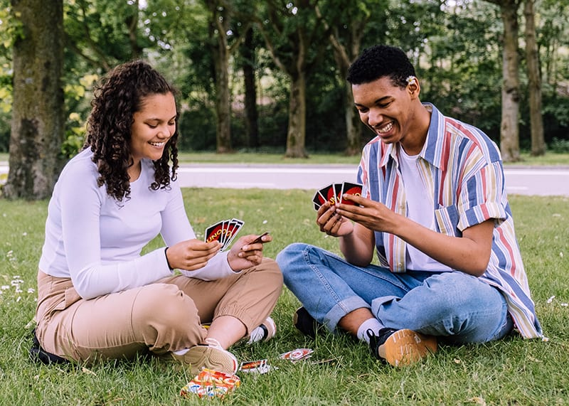 man and woman sitting on grass playing cards