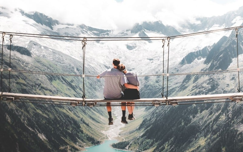 Man and woman sitting on hanging bridge at daytime