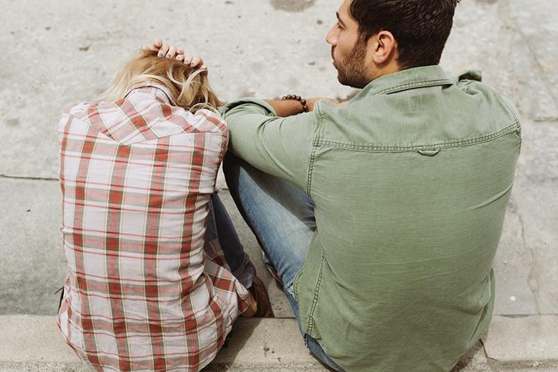 man and woman sitting on sidewalk while talking