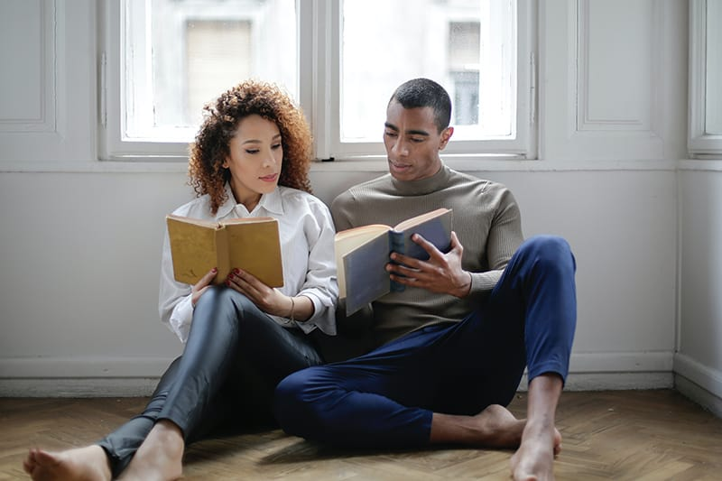 man and woman sitting on the floor reading the book
