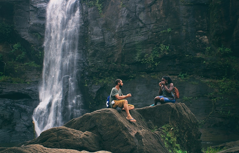 man and woman sitting on the rock near the waterfall