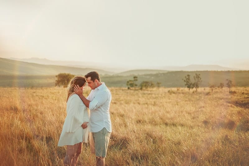 man and woman standing in brown grass field
