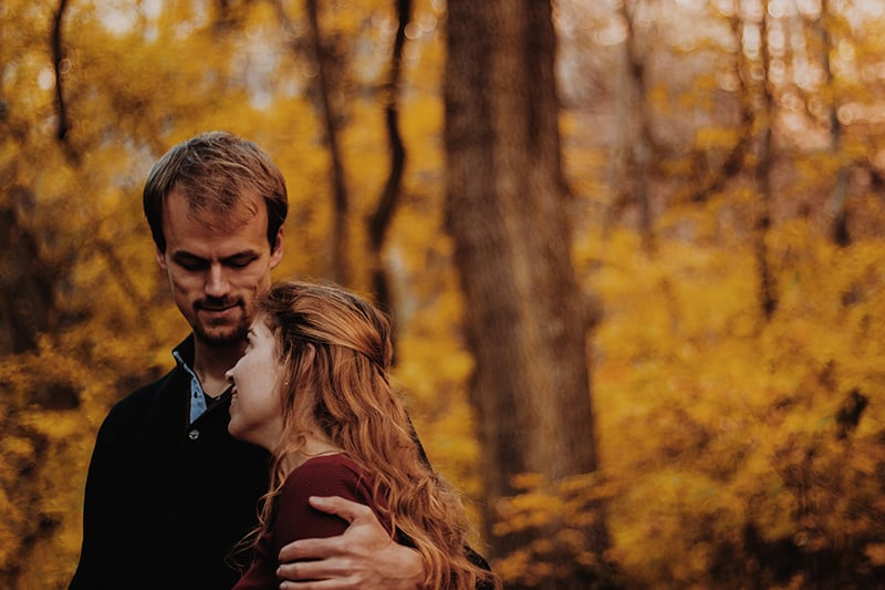 man and woman standing in the wood while hugging each other