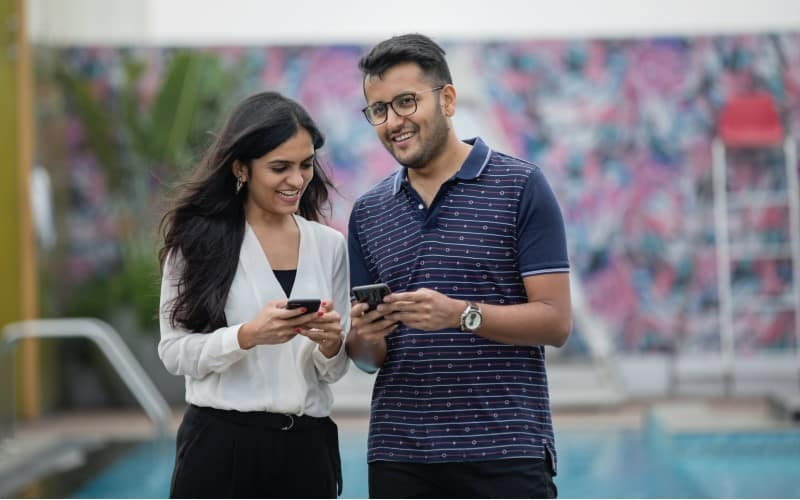 man and woman standing n the street with phones in their hands smiling