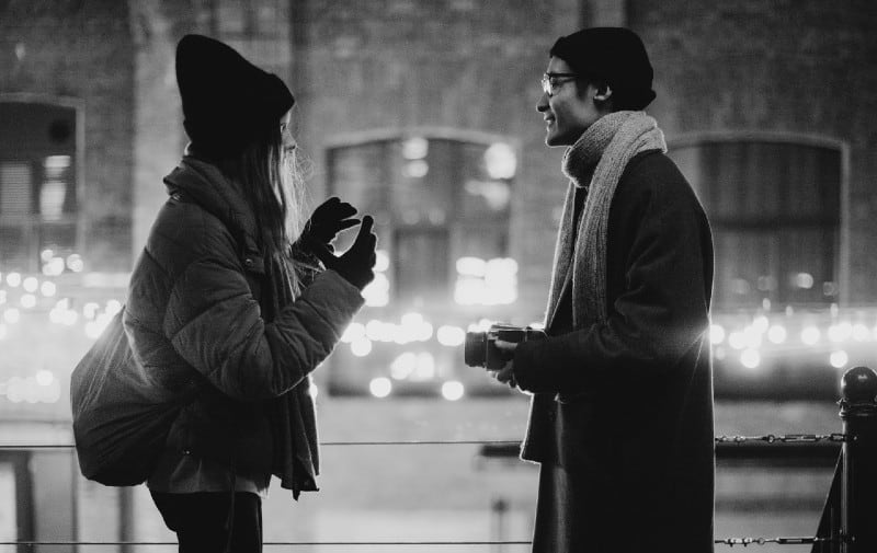Man and woman talking on the street in the evening